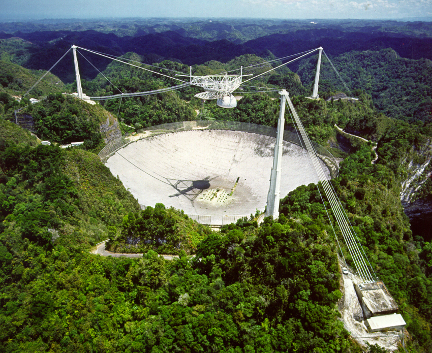 The Arecibo radio telescope is situated approximately 15 km from Arecibo in the island of Puerto Rico It is the largest single-aperture telescope that has ever been built. In fact it has a 305 metre wide antenna, and for this reason it has been built inside a natural cavity. Credits: Cornell University, NSF, NASA