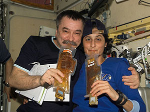 The Russian cosmonaut, Mikhail Tyurin and the American astronaut Sunita Williams pose for a photograph while drinking. Credits: NASA